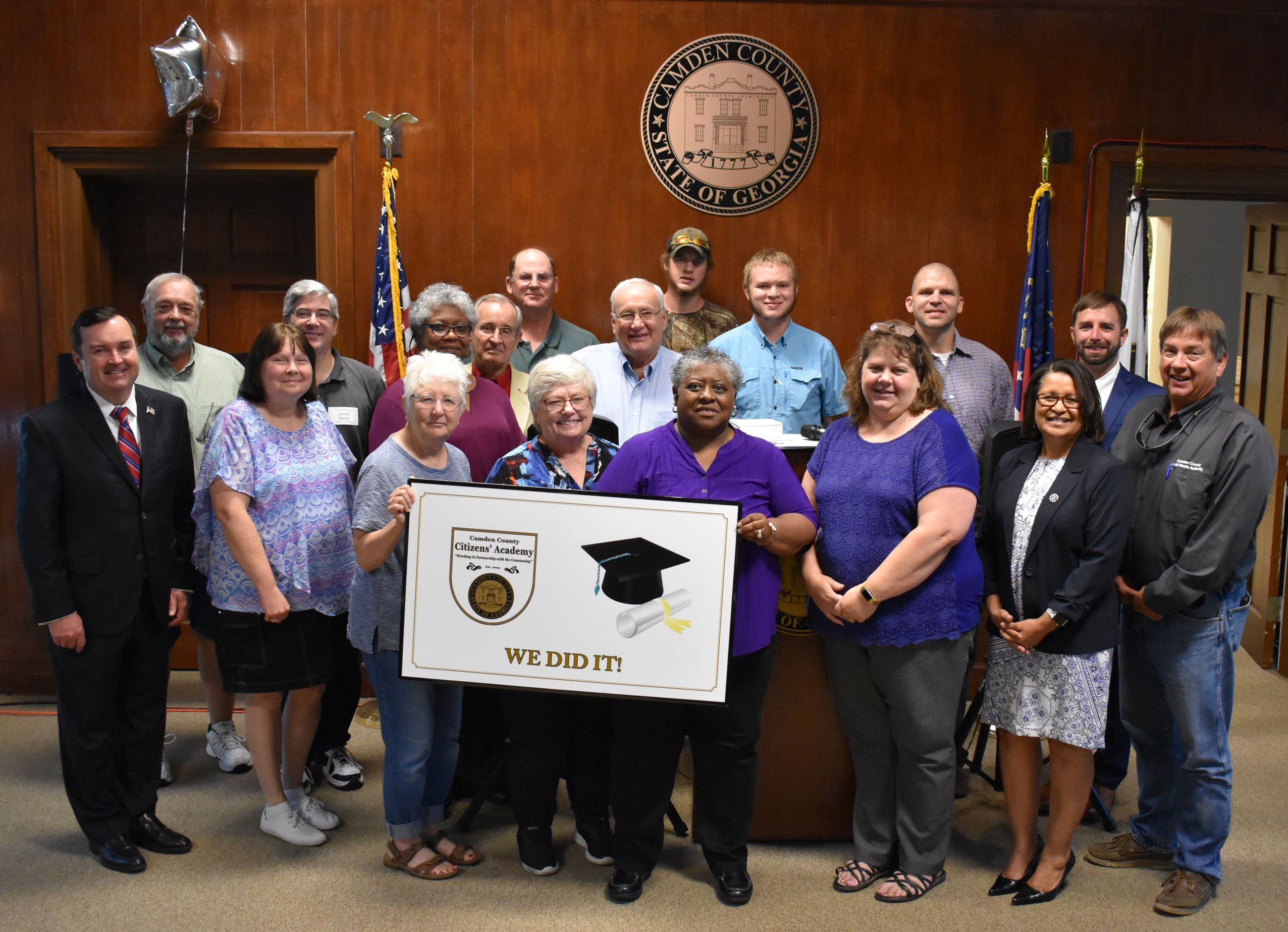 "County Staff and Commissioners posing with Citizens' Academy Graduates with a sign stating ""we"